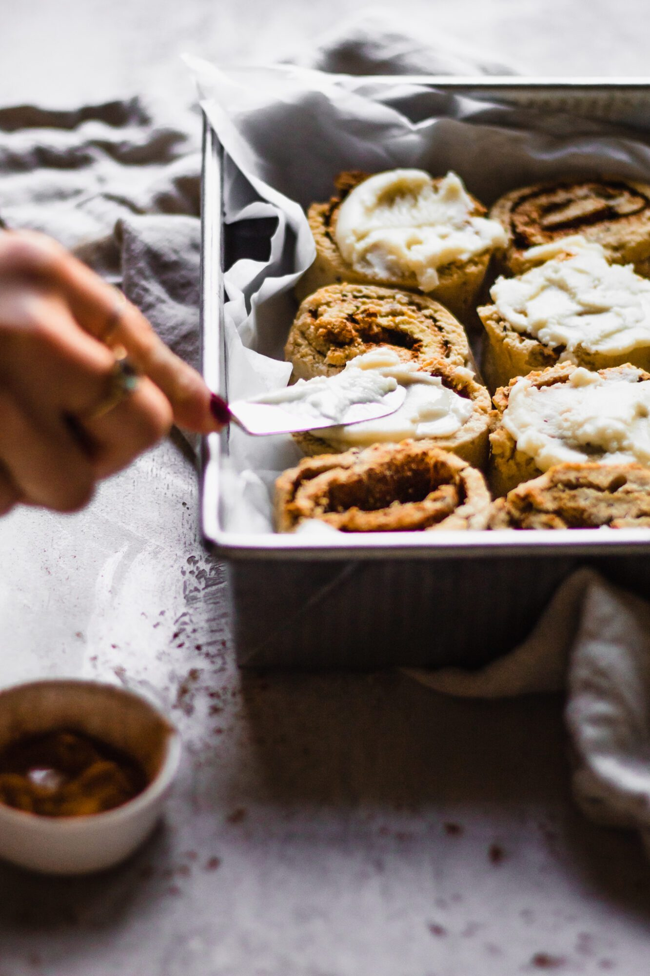 hand icing cinnamon rolls
