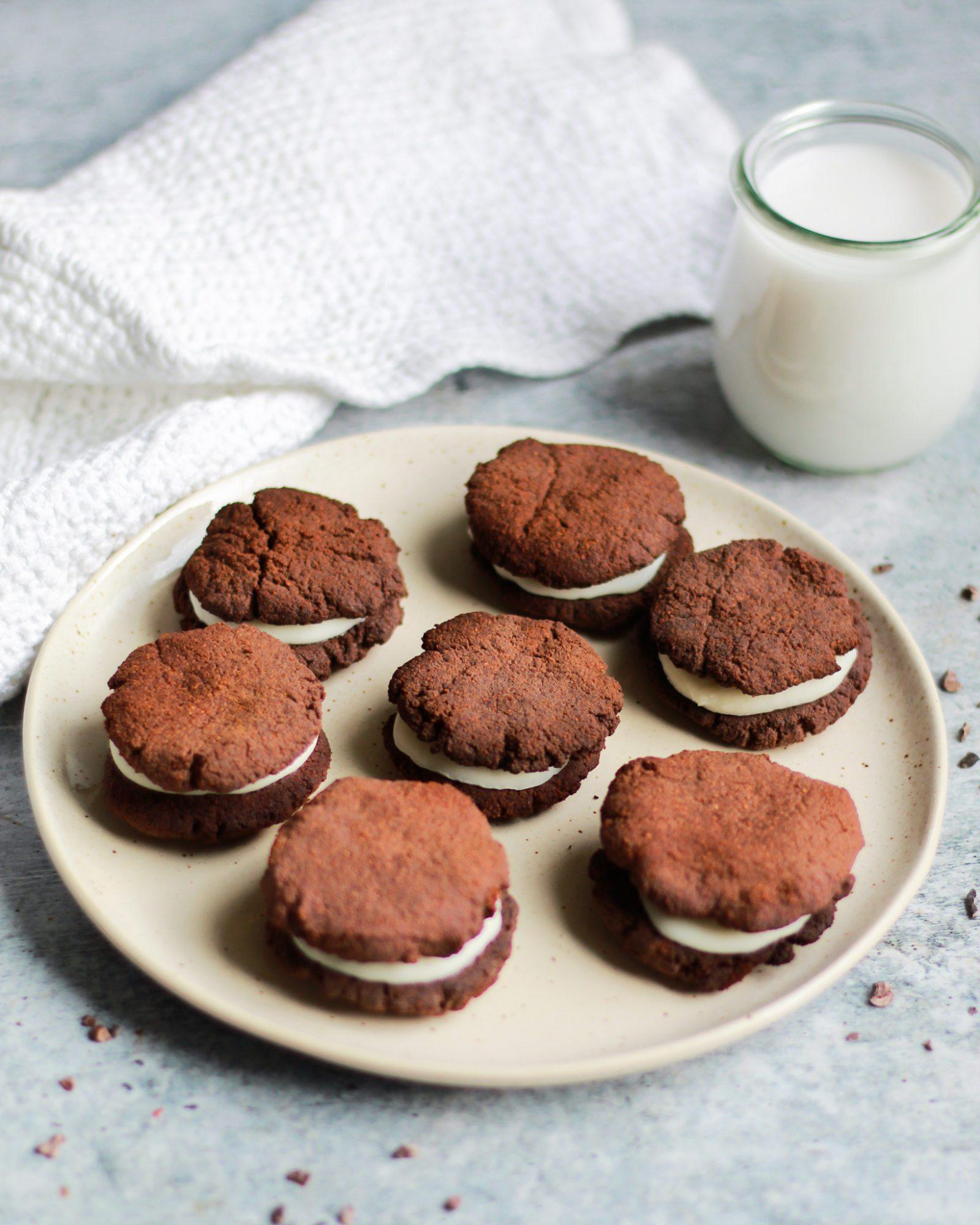 plate of paleo vegan oreos on a plate next to almond milk