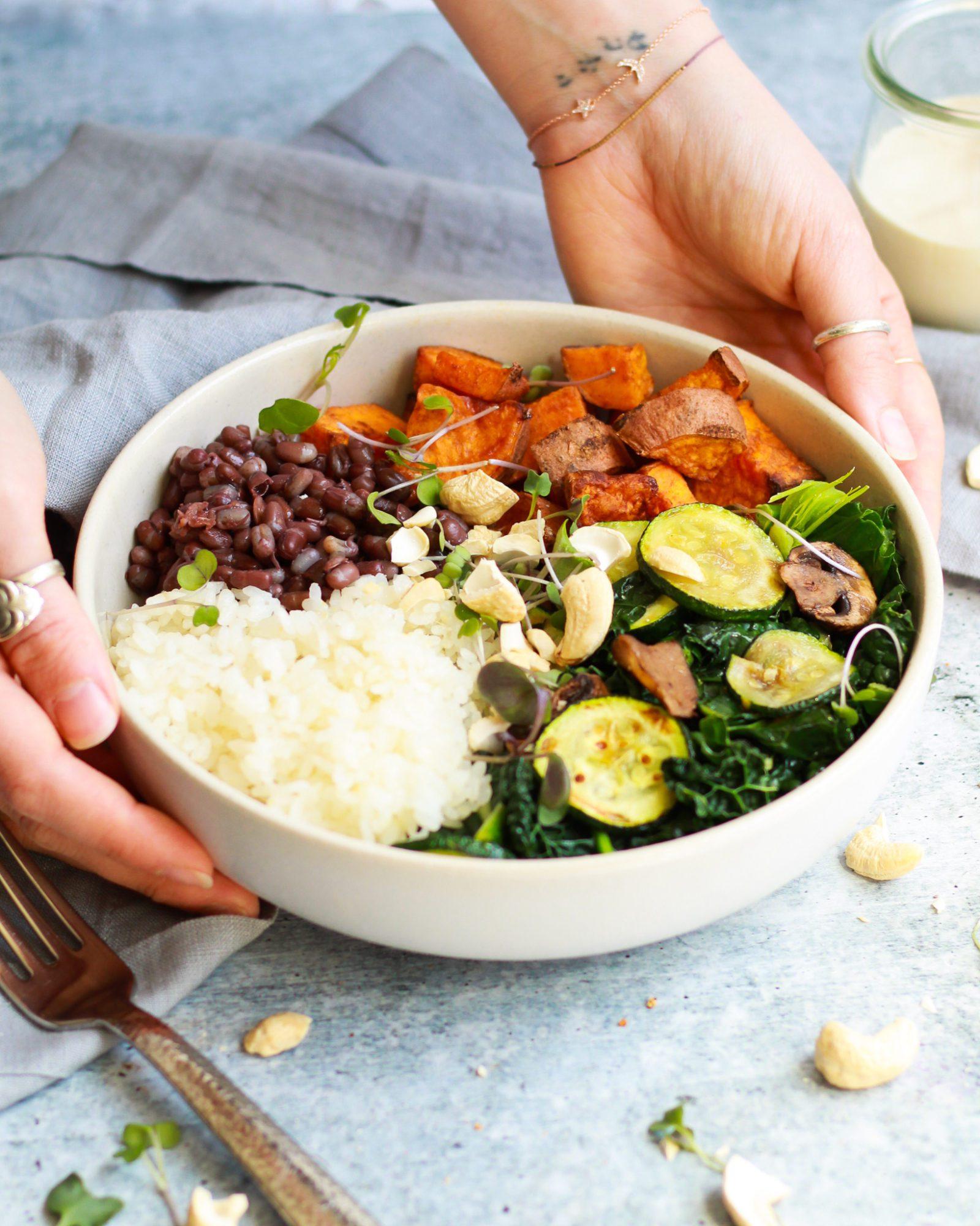 3/4 shot of macrobiotic bowl held by hands with vegan tahini sauce