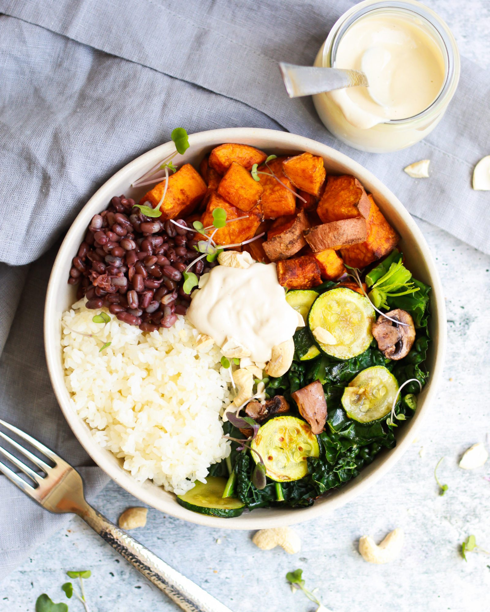 overhead shot of macrobiotic bowl drizzled in the best tahini sauce