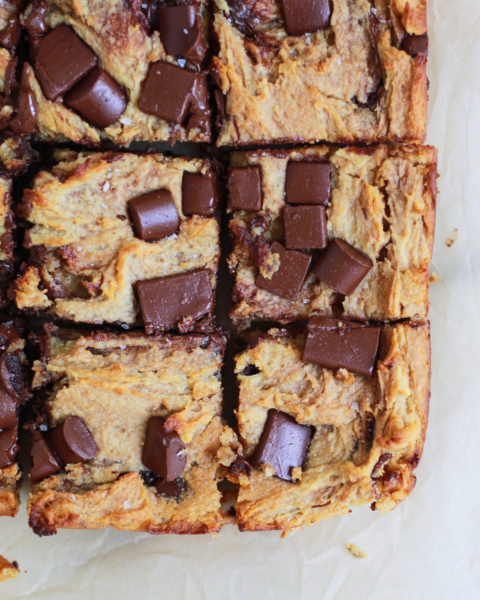 close up of chocolate chip blondies on parchment paper