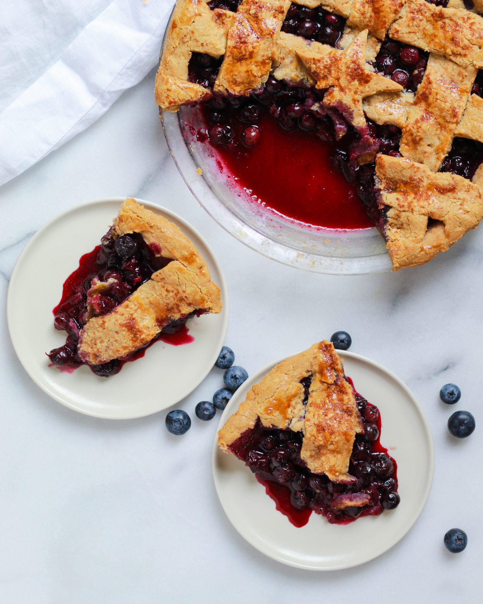 overhead shot of two slices of blueberry pie with full blueberry pie