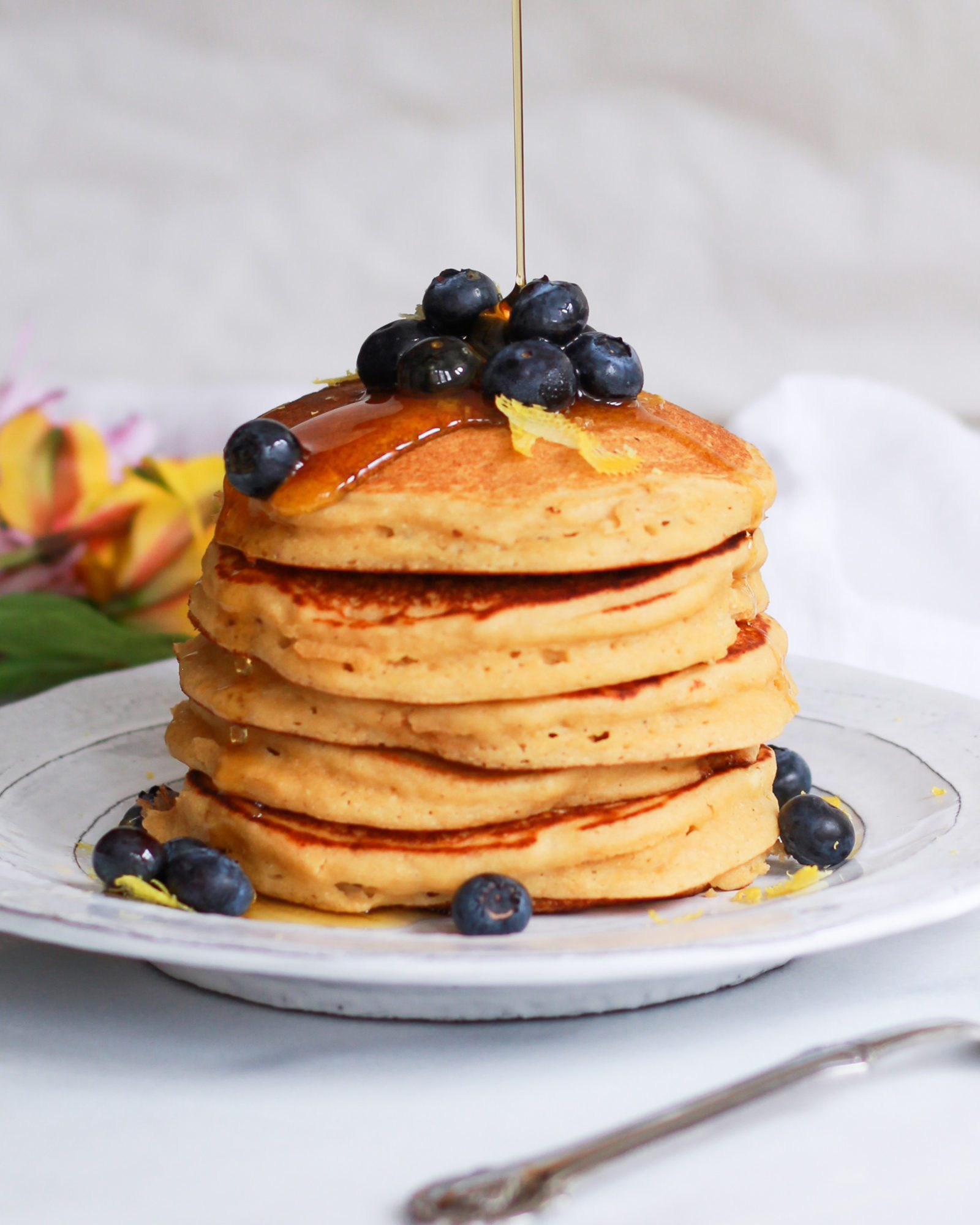 drizzle of maple syrup over lemon pancakes