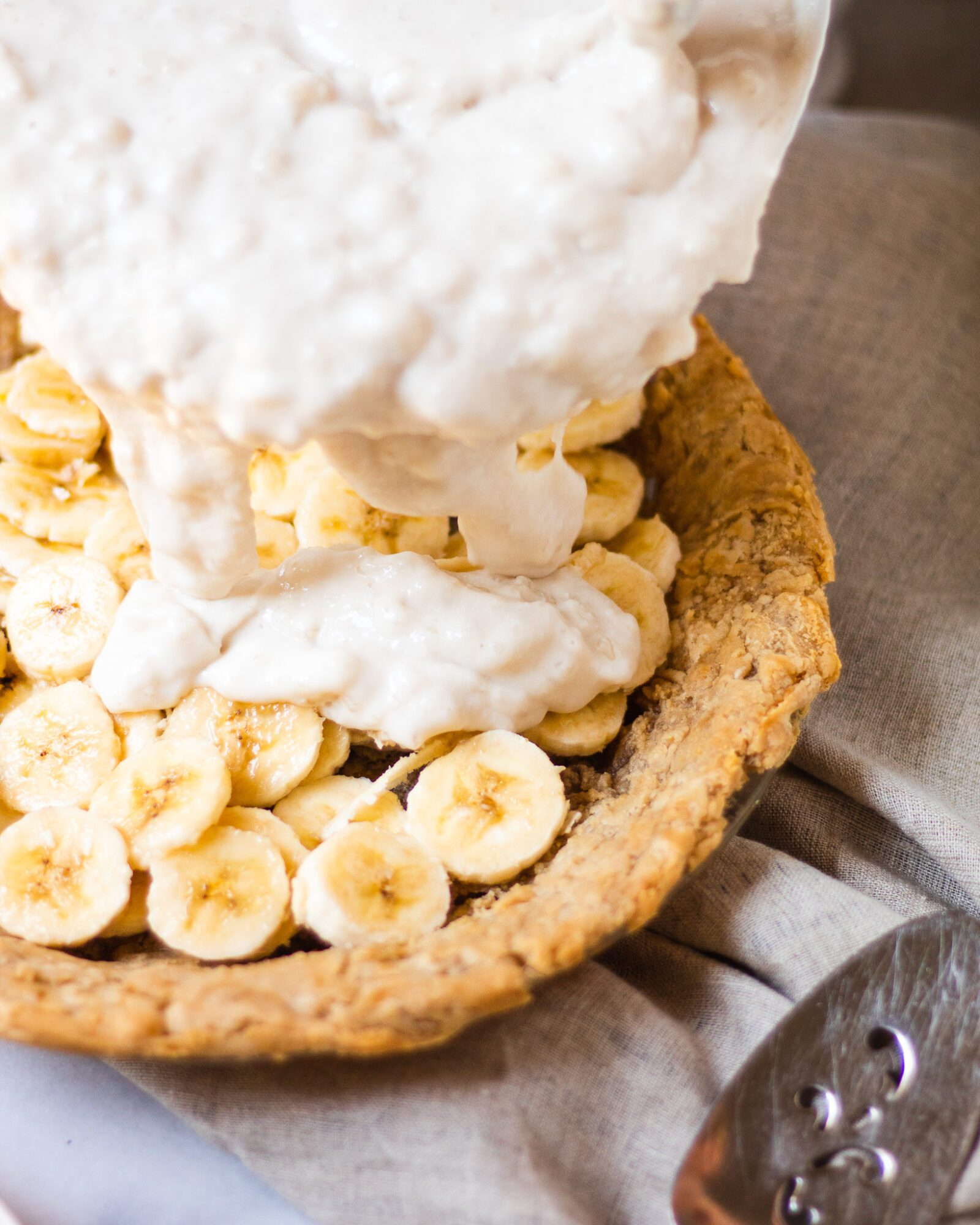 pouring vanilla pudding on top of bananas in pie crust