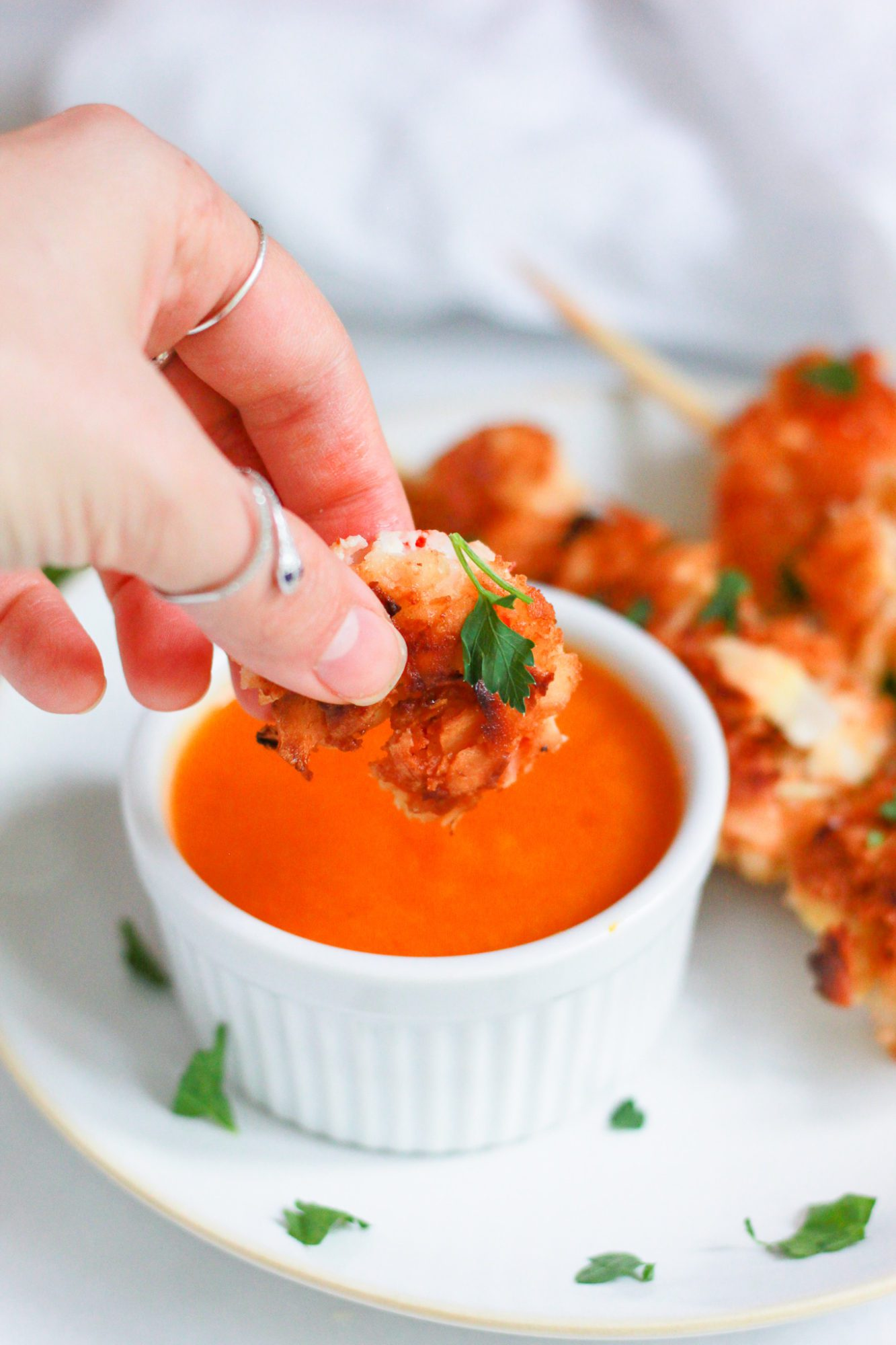 hand dipping coconut shrimp into apricot dipping sauce