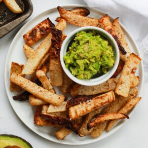 baked jicama fries on plate with mashed avocado