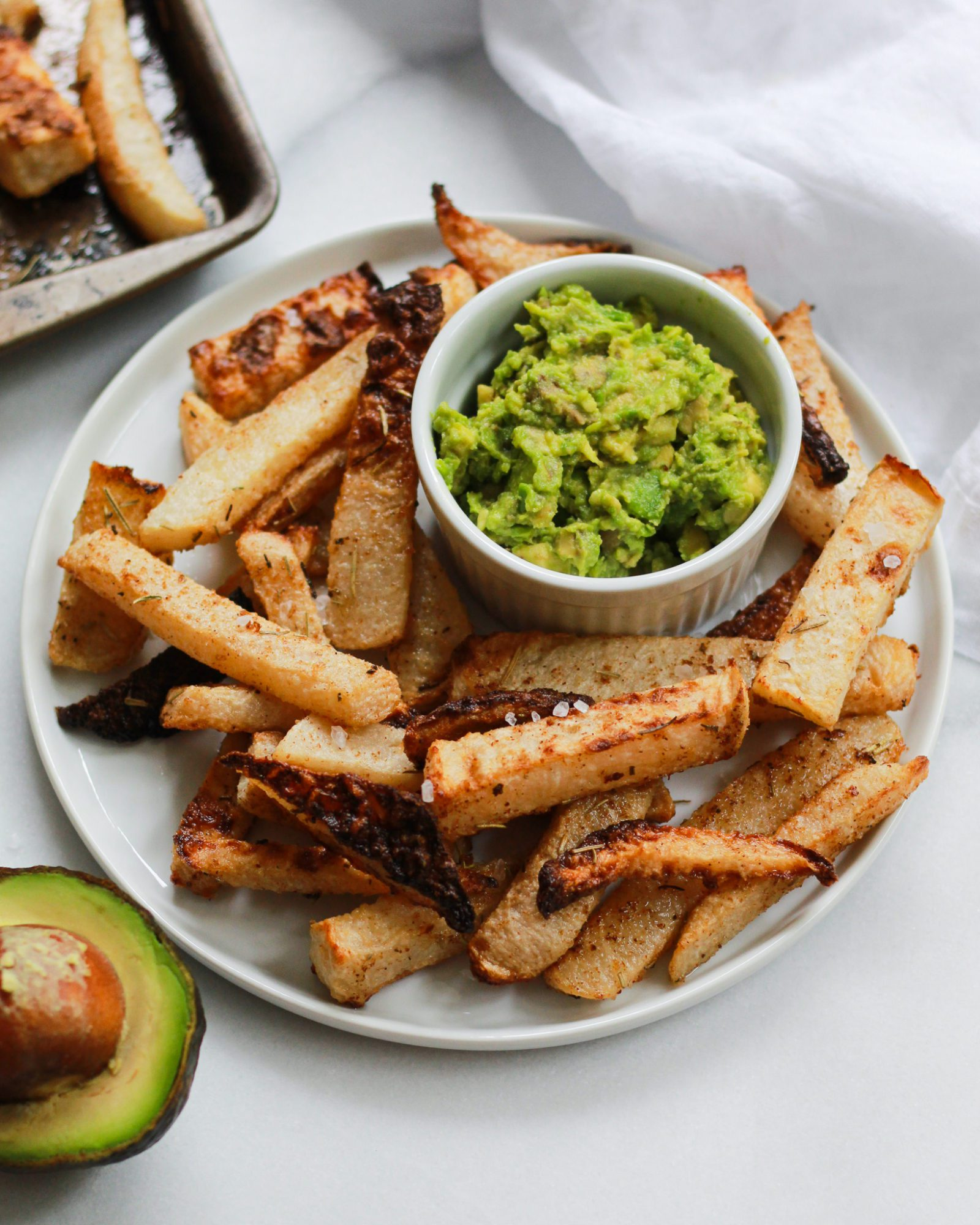 white plate with jicama fries and guacamole