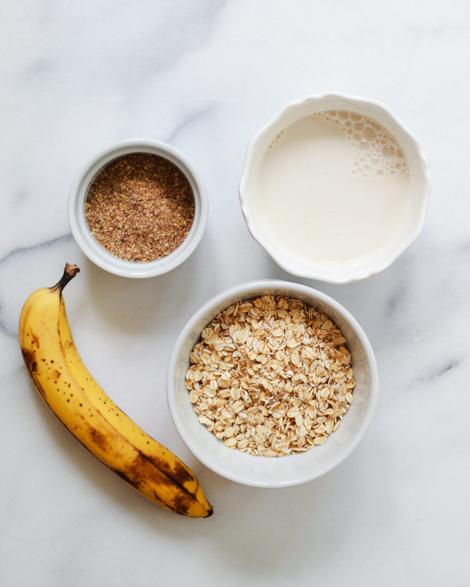 banana, oats, flaxseed, and almond milk on counter