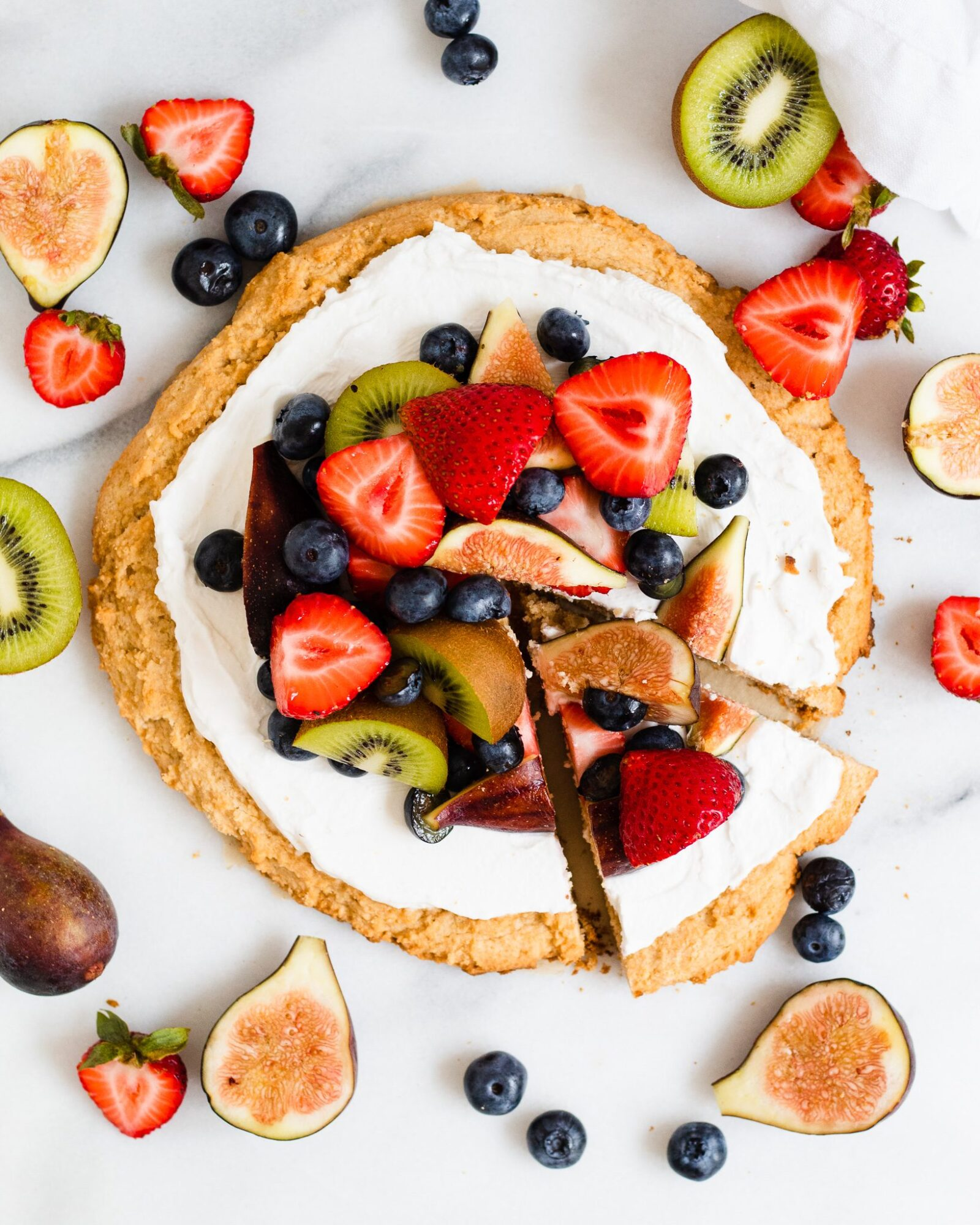 full vegan fruit pizza with slice out of it