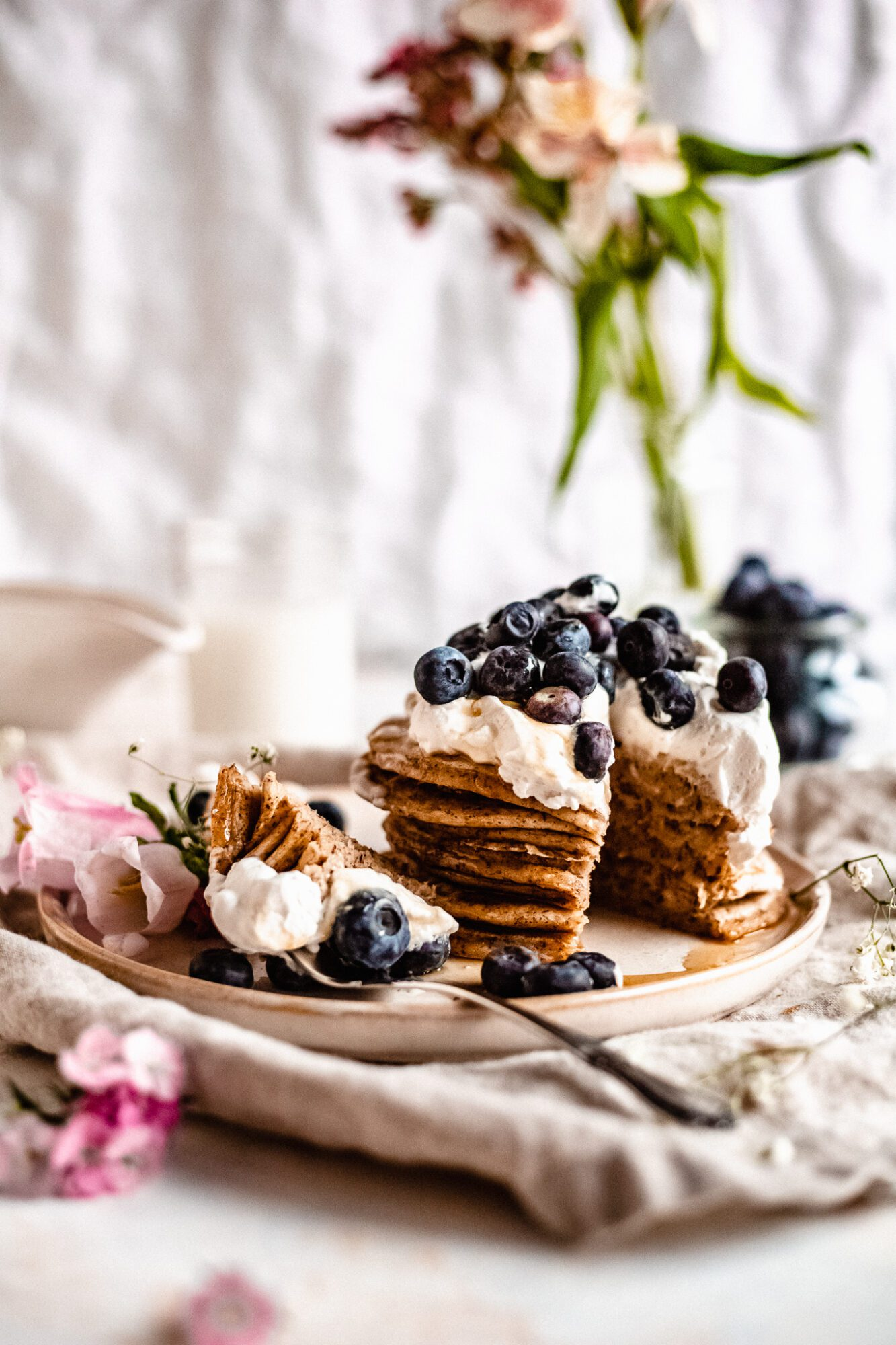 sliced gluten free pancakes with whipped cream and blueberries