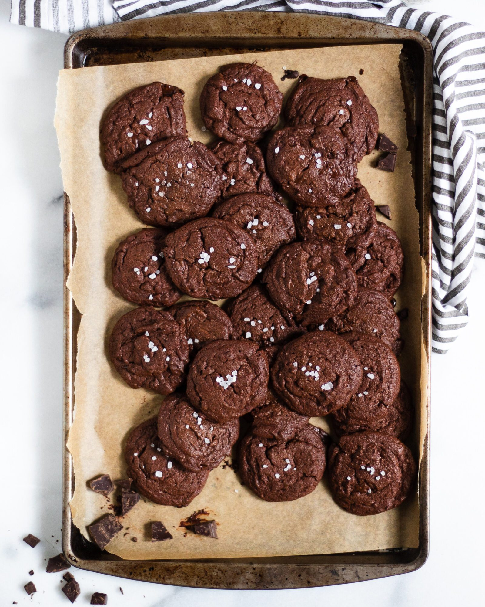 baking sheet full of chocolate cookies with a sprinkle of sea salt