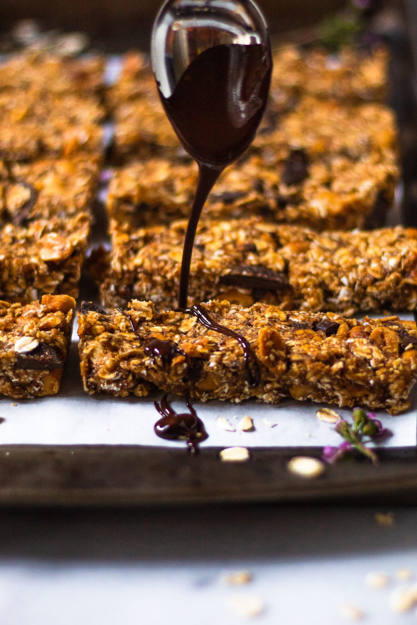 spoon drizzling chocolate over no bake granola bars
