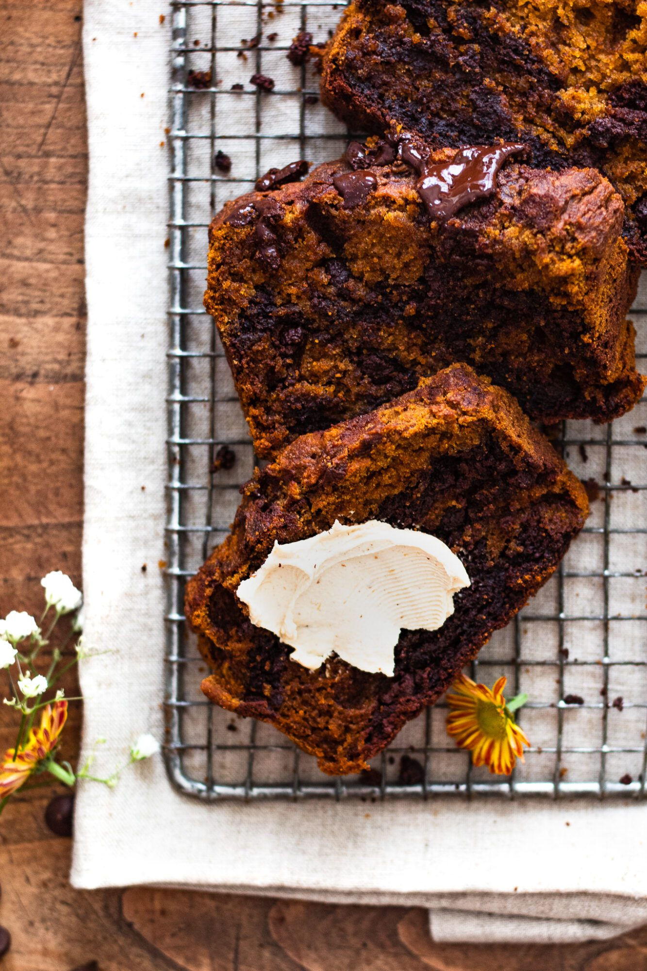 slices of pumpkin bread on cooling rack with vegan cream cheese