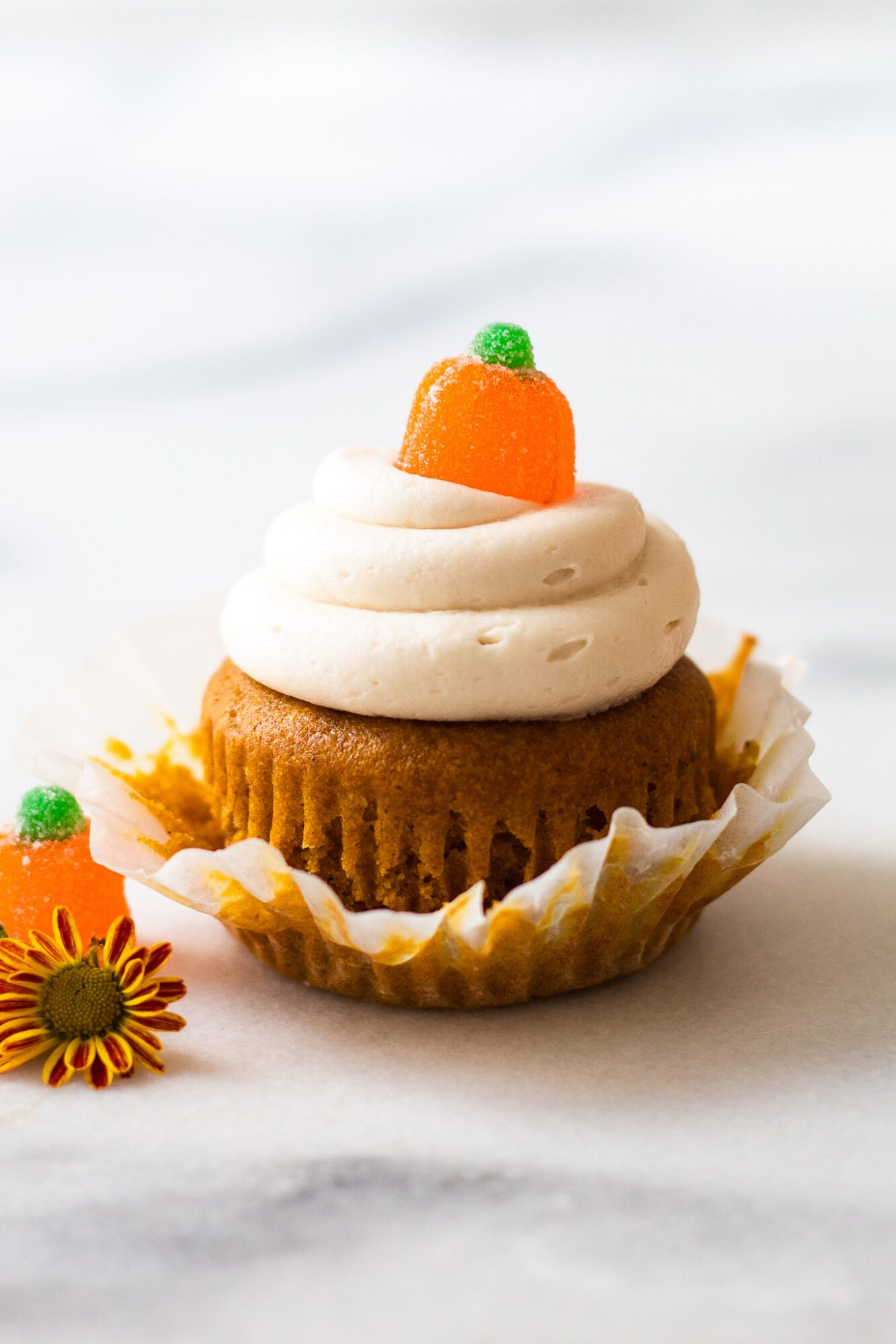 pumpkin cupcake with cupcake liner pulled down