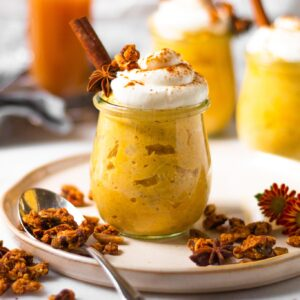 healthy oatmeal jars with whipped cream and granola sprinkled around them