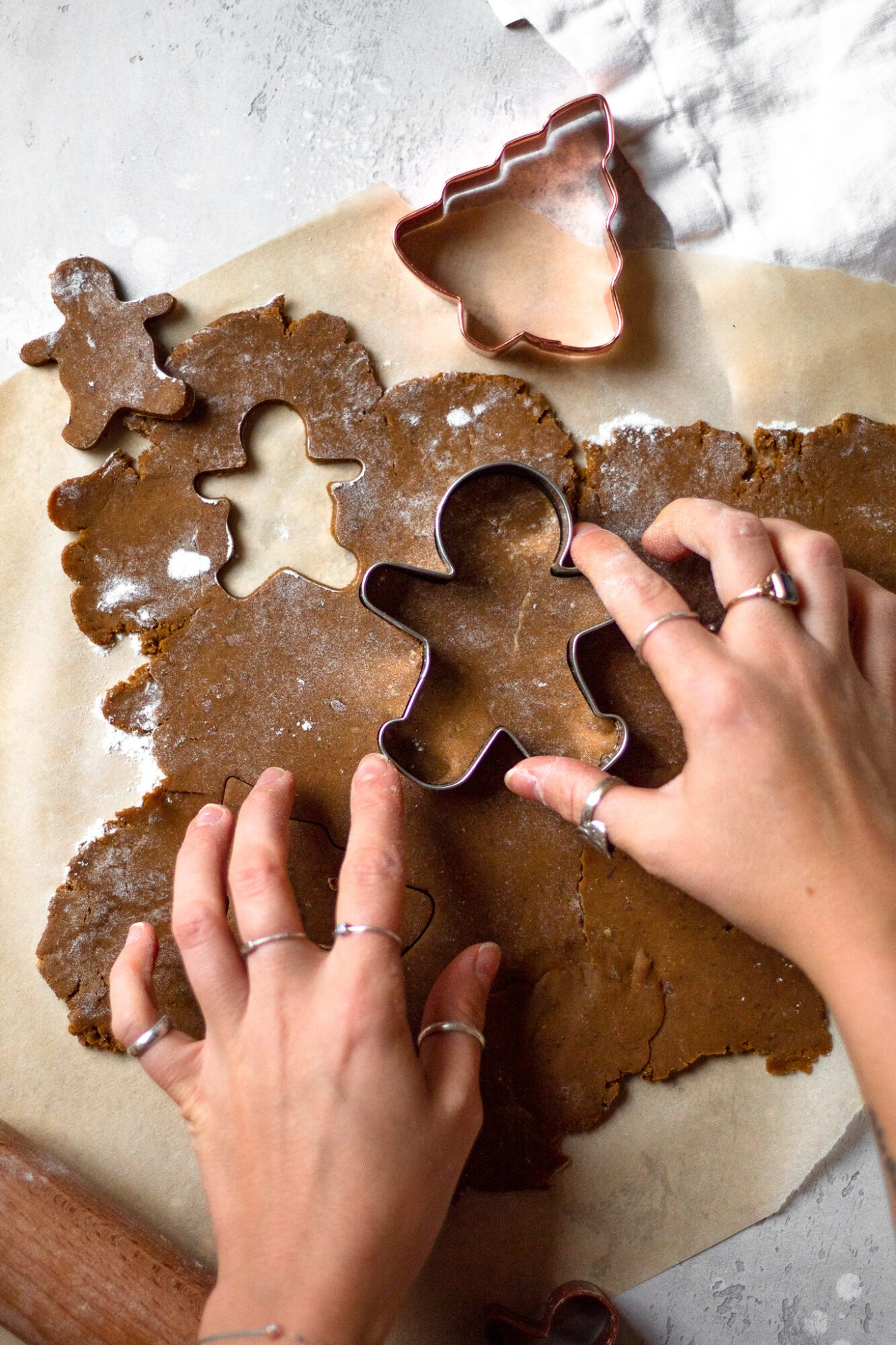 hand pressing cookie cutter into dough