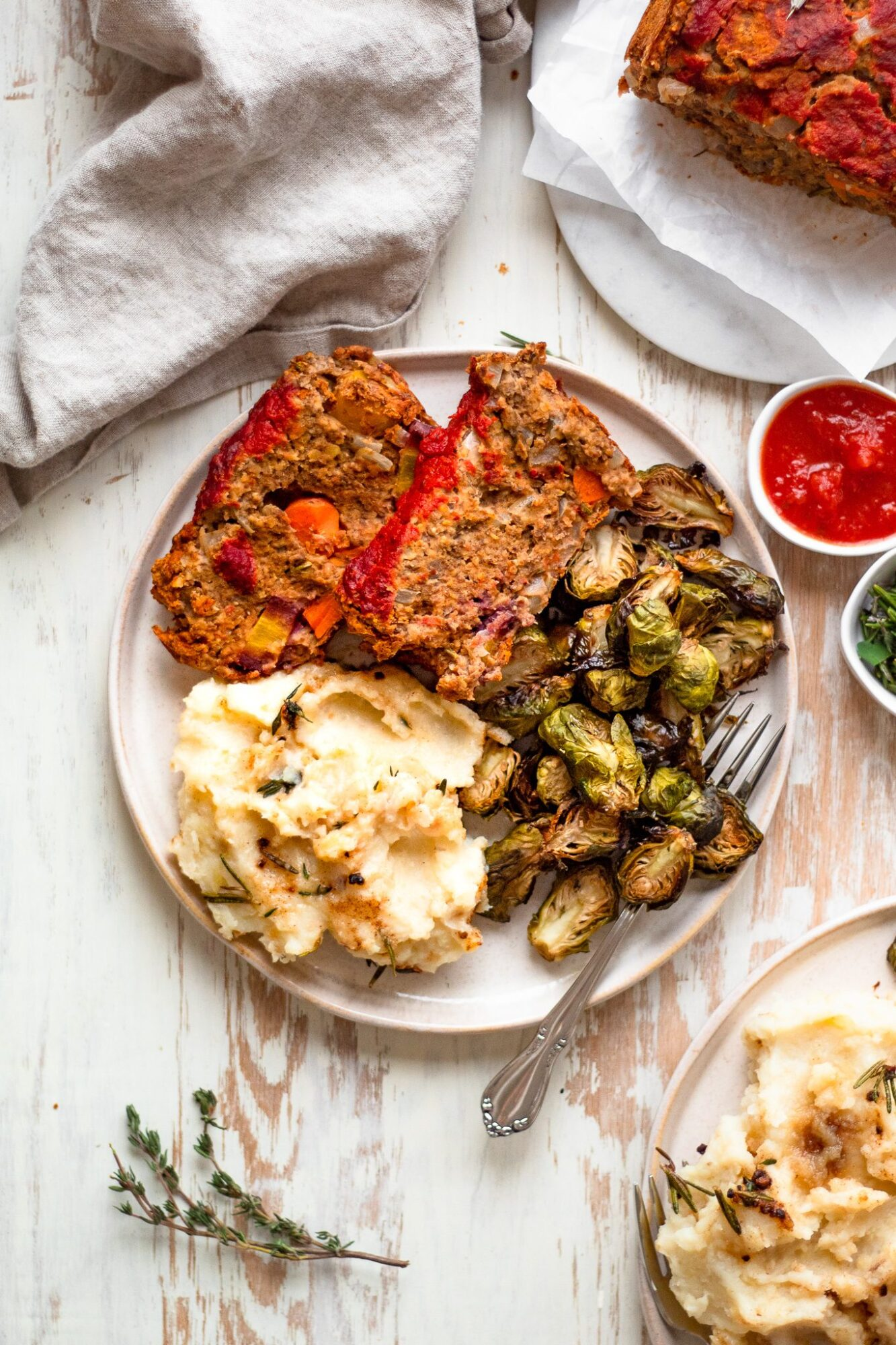 overhead of plate with lentil meatloaf, mashed potatoes, and brussels sprouts