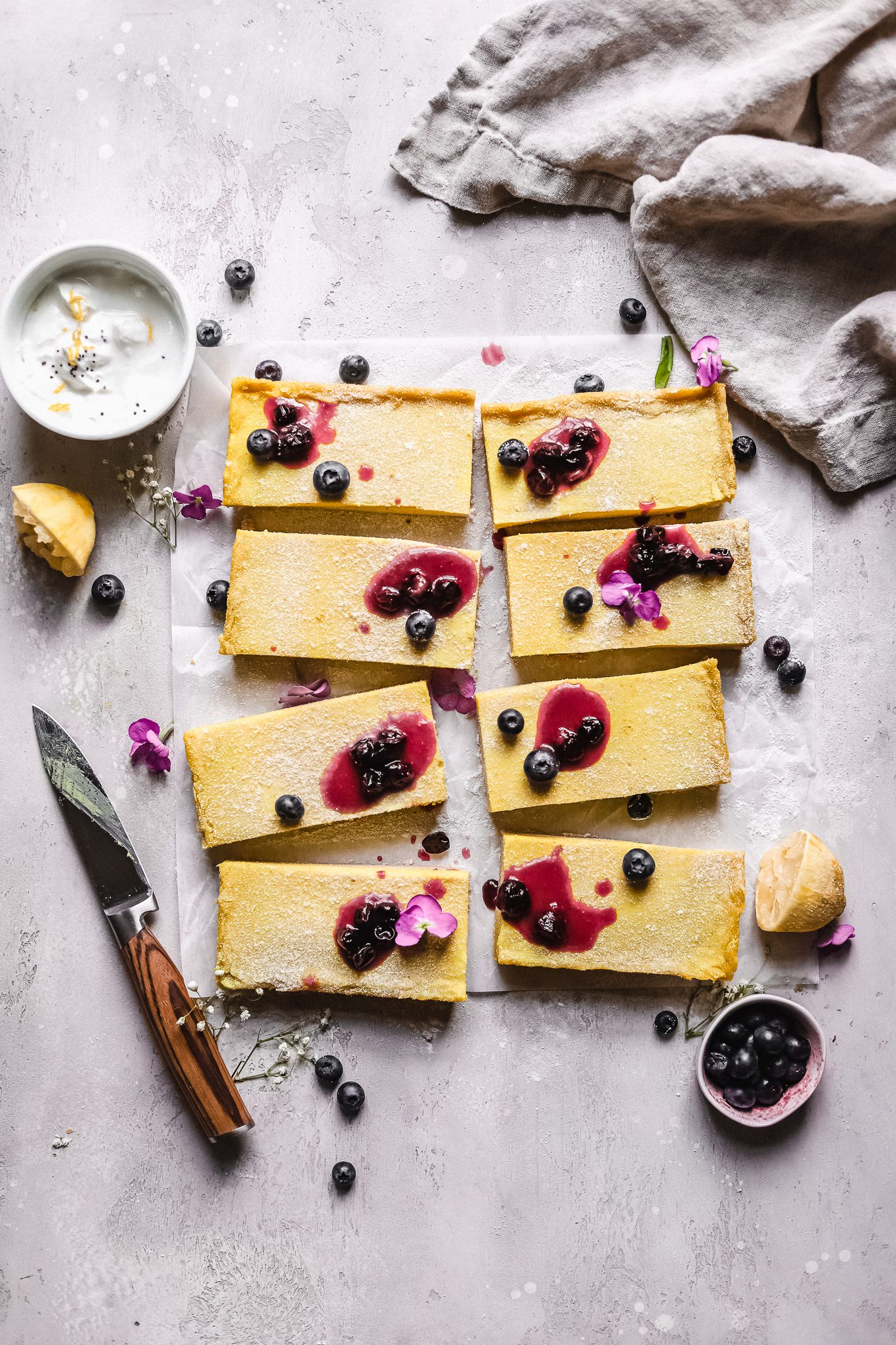 sliced Paleo vegan lemon bars with blueberry jam on top with a knife next to it