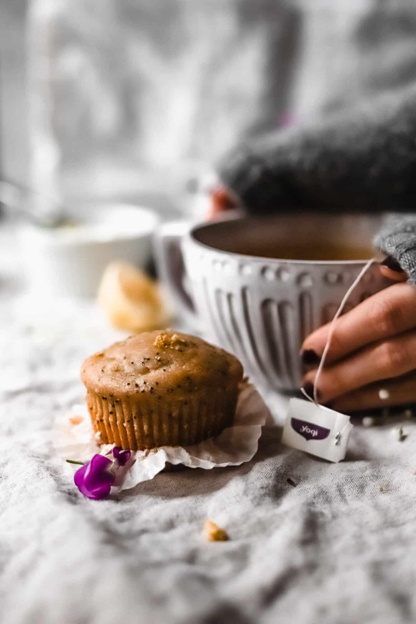 hand holding tea mug with lemon poppy seed muffin