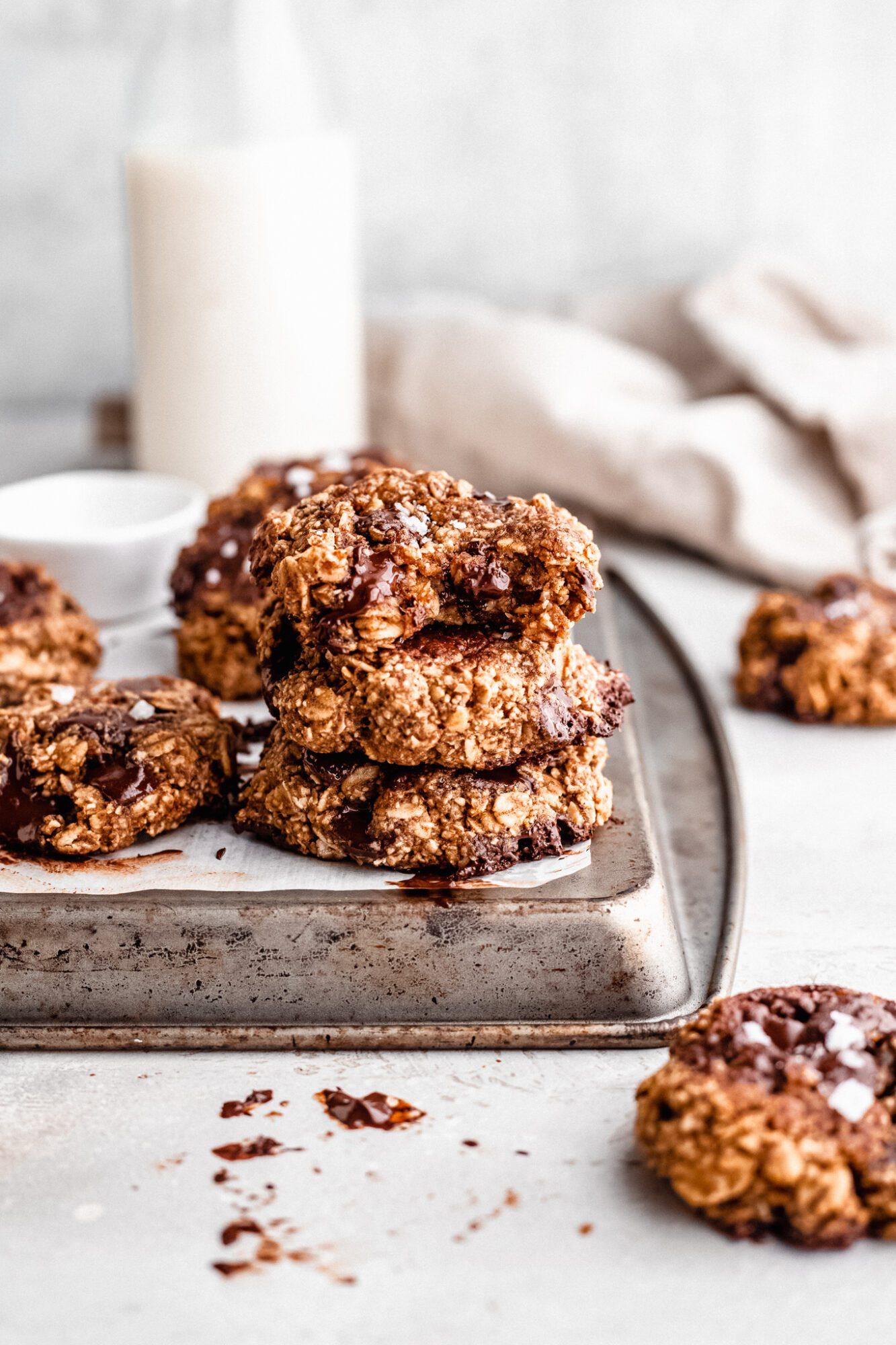 vegan oatmeal cookies stacked on baking sheet