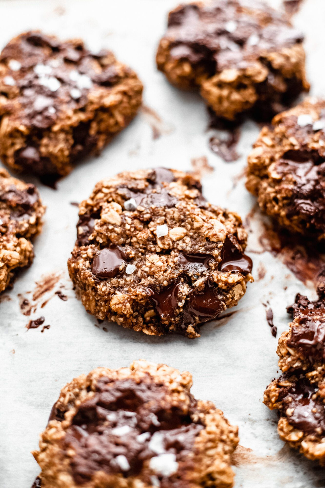gluten free vegan chocolate chip oatmeal cookies on parchment paper