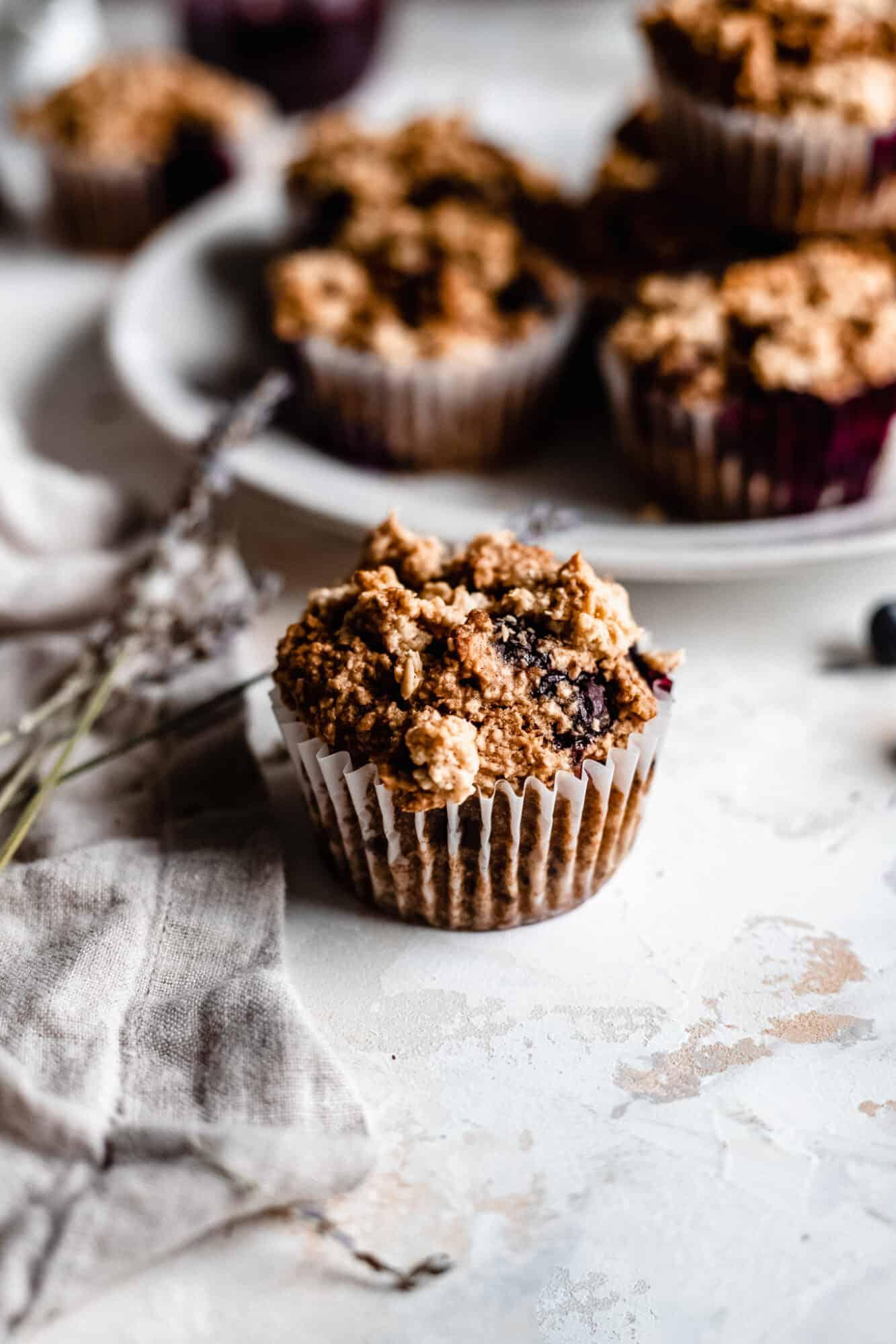 oatmeal blueberry muffin next to plate of muffins