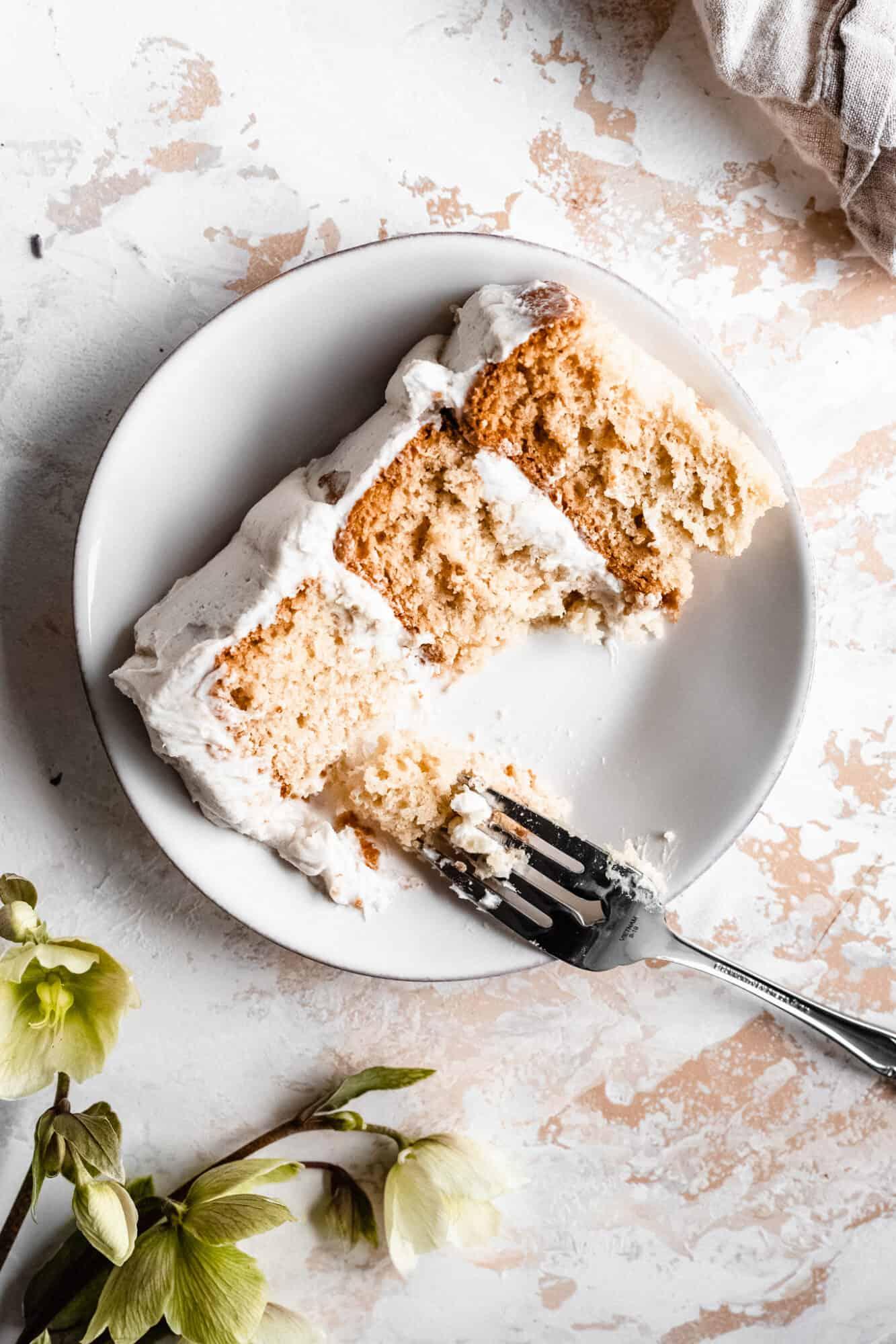 slice of vegan vanilla cake with bite taken from it