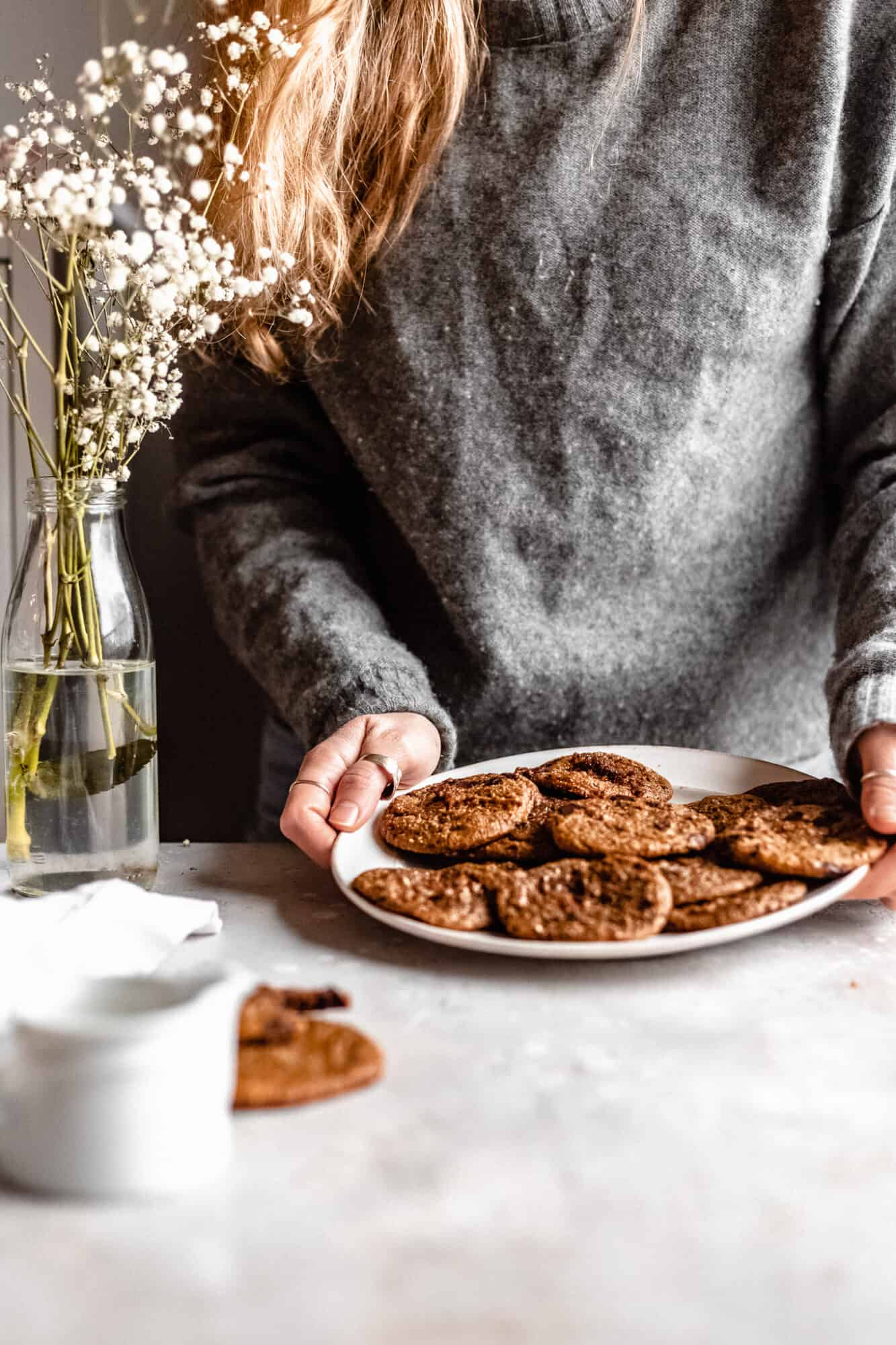 hand placing chocolate chip cookies down