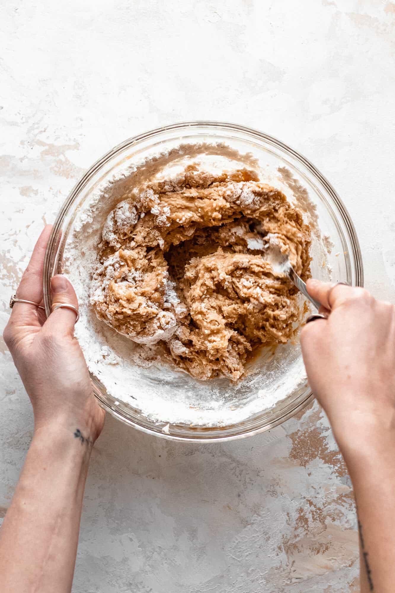 hand folding peanut butter cookie batter