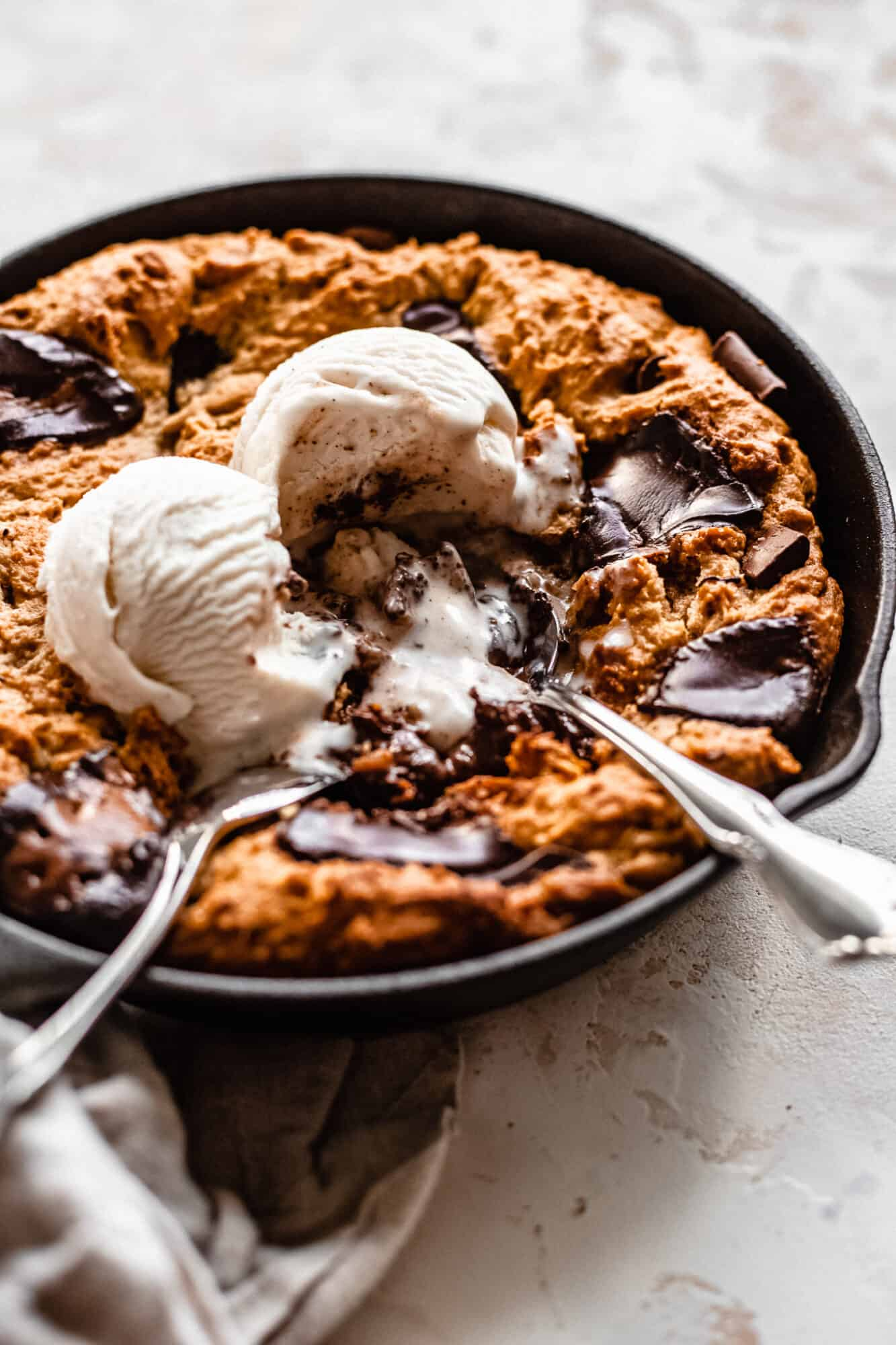 spoons eating melted ice cream on top of cookie skillet