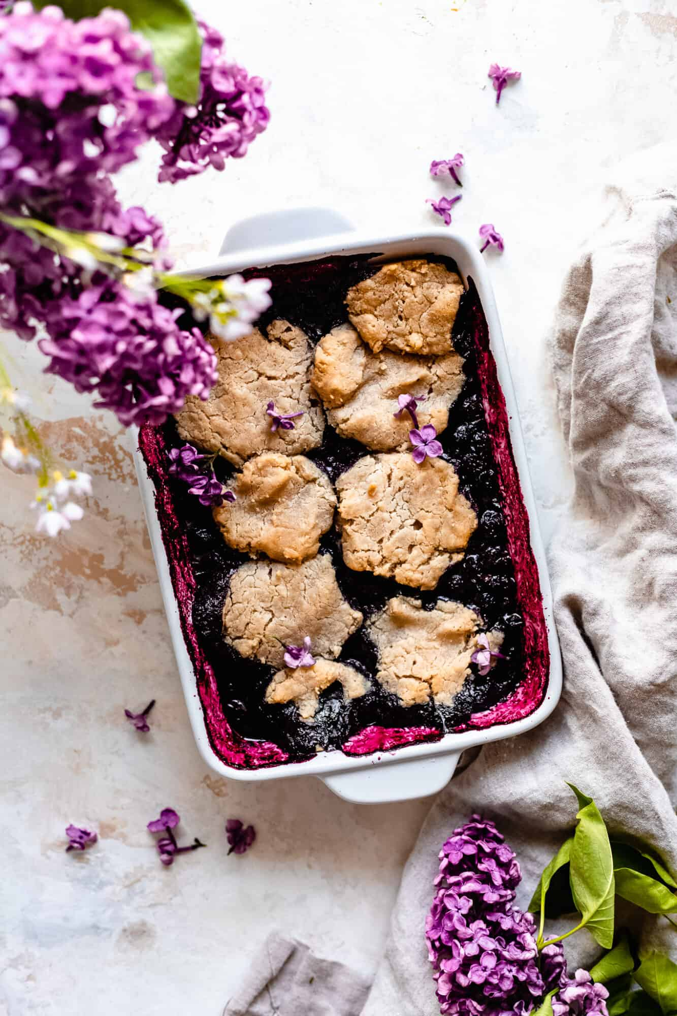 white dish with healthy blueberry cobbler
