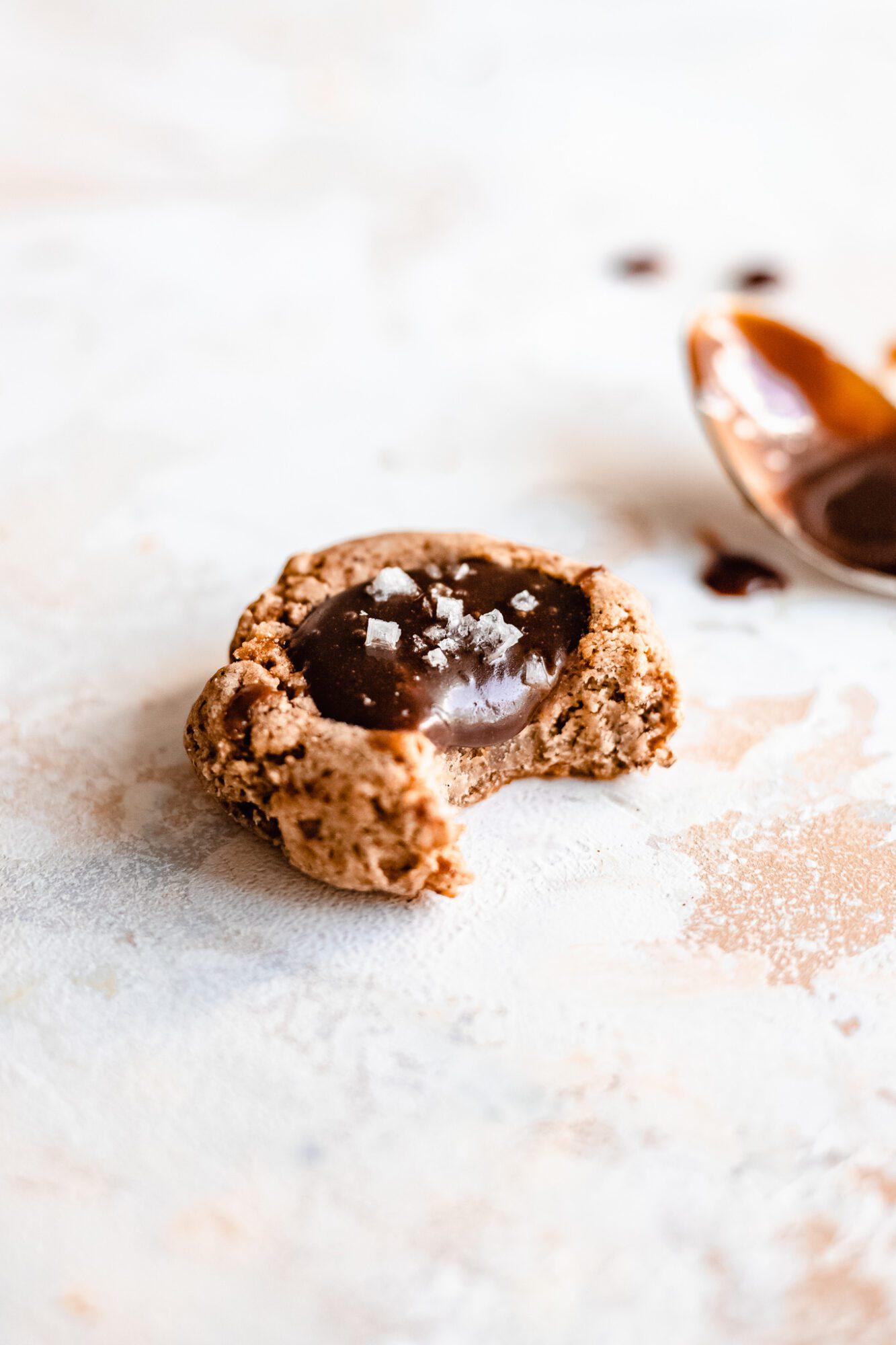 bitten paleo caramel thumbprint cookie with caramel spoon