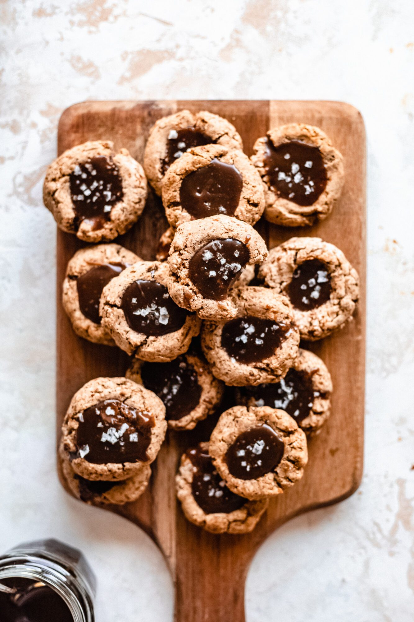 wooden board with caramel thumbprint cookies stacked