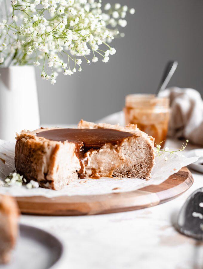 sliced baked vegan vanilla cheesecake with caramel sauce on wooden board