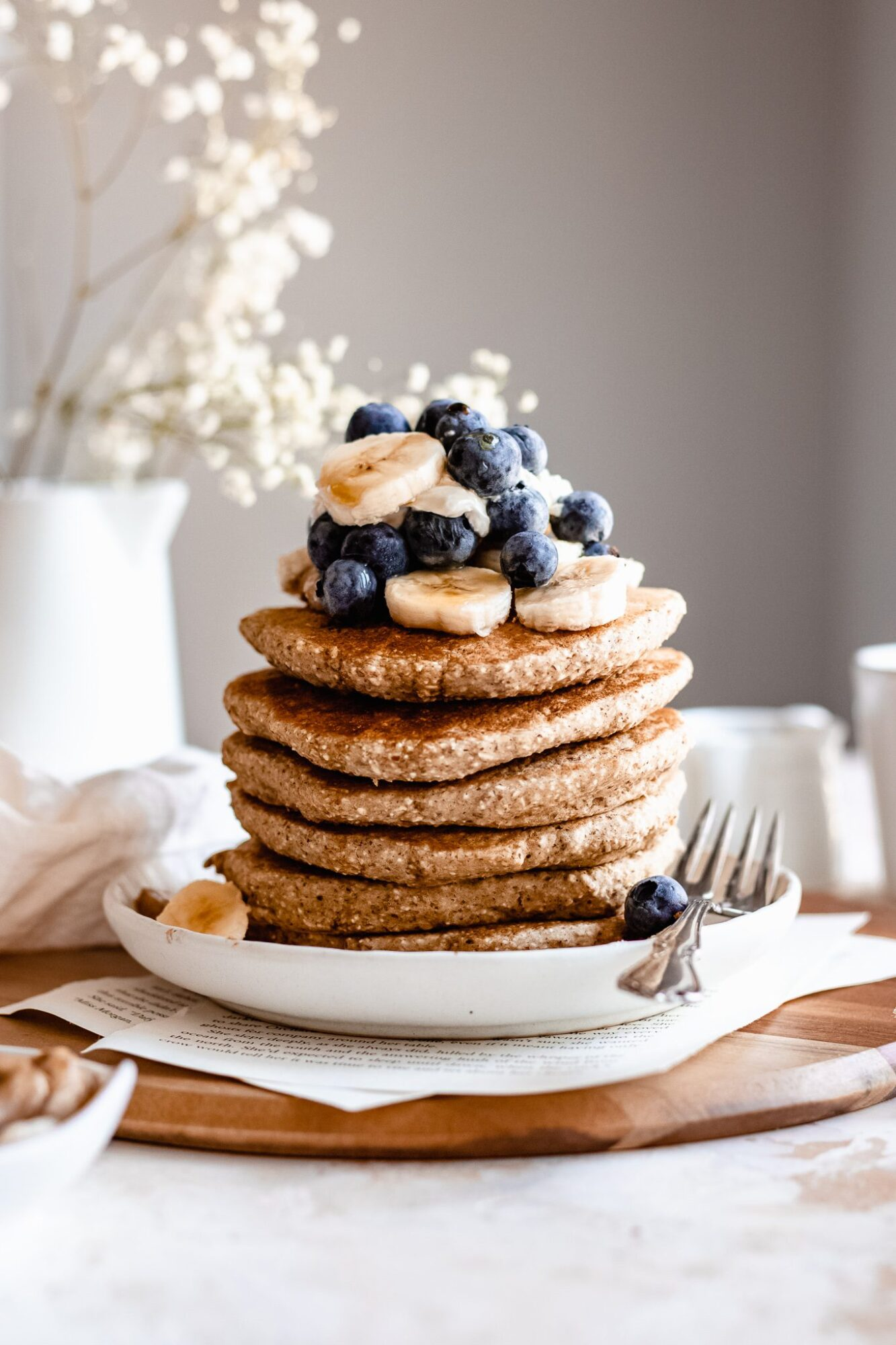 stack of fluffy banana oatmeal pancakes on wooden board with blueberries and bananas