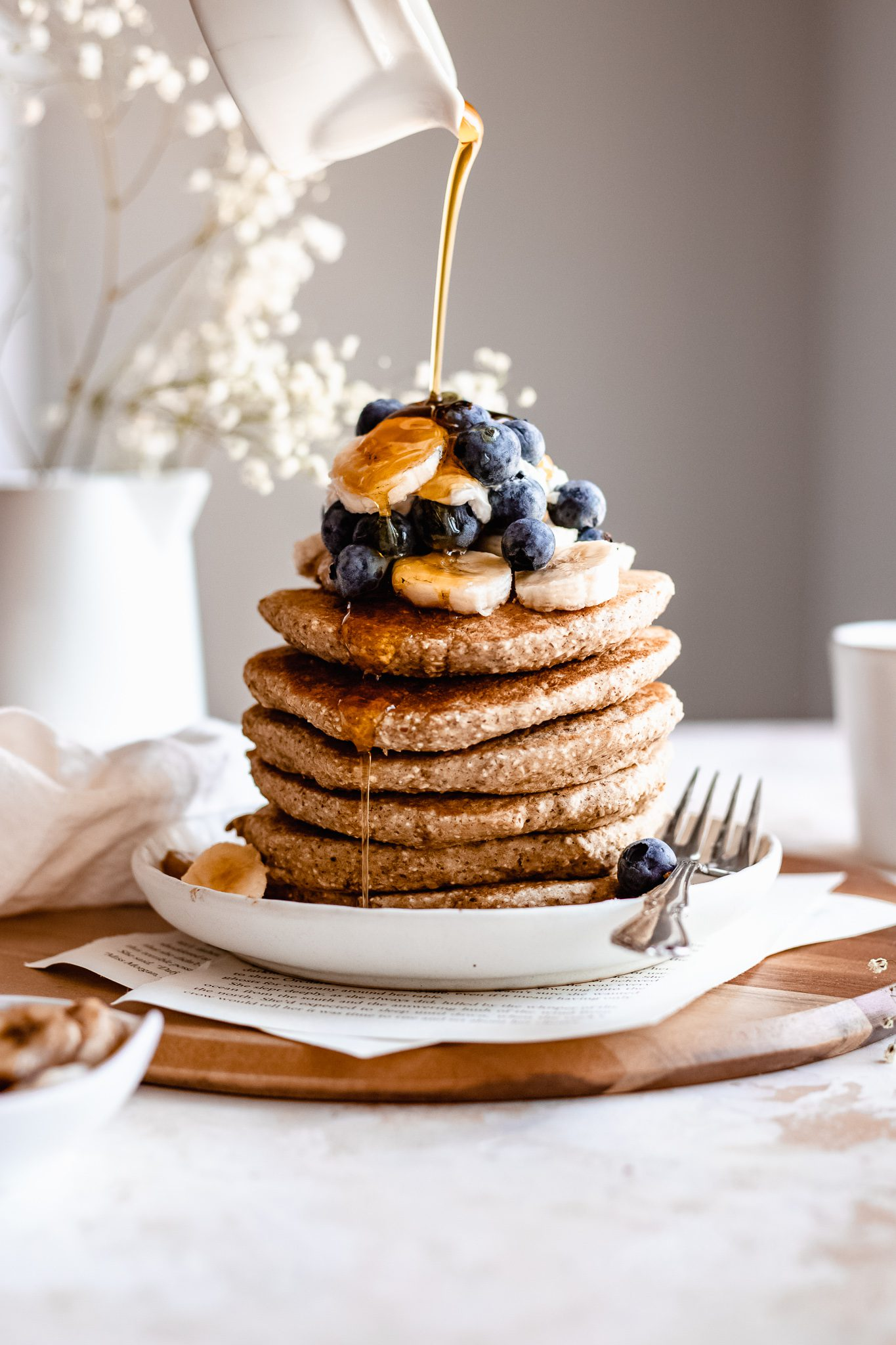 Hand drizzle maple syrup on top of oatmeal pancakes topped with banana and blueberries