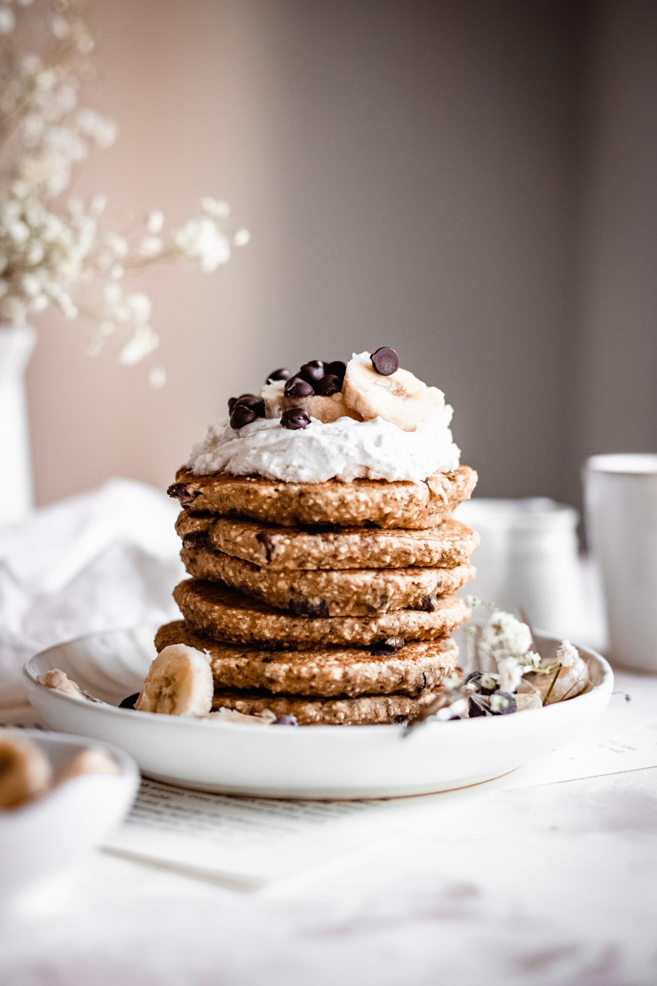 stack of oatmeal pancakes with coconut whipped cream and chocolate chips