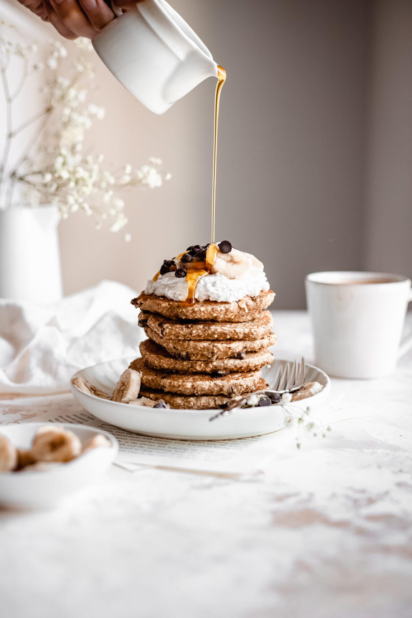 hand drizzle maple syrup on healthy chocolate chip pancakes