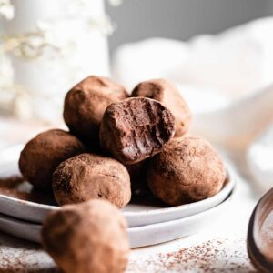 chocolate truffles with bite taken on grey plate