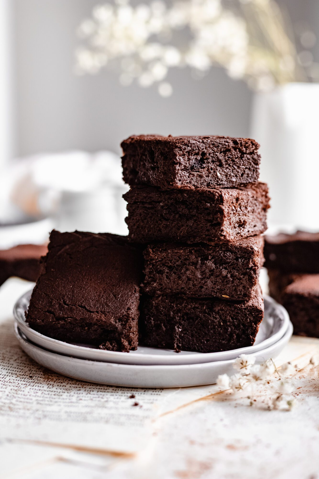 paleo vegan sweet potato brownies stacked on parchment paper
