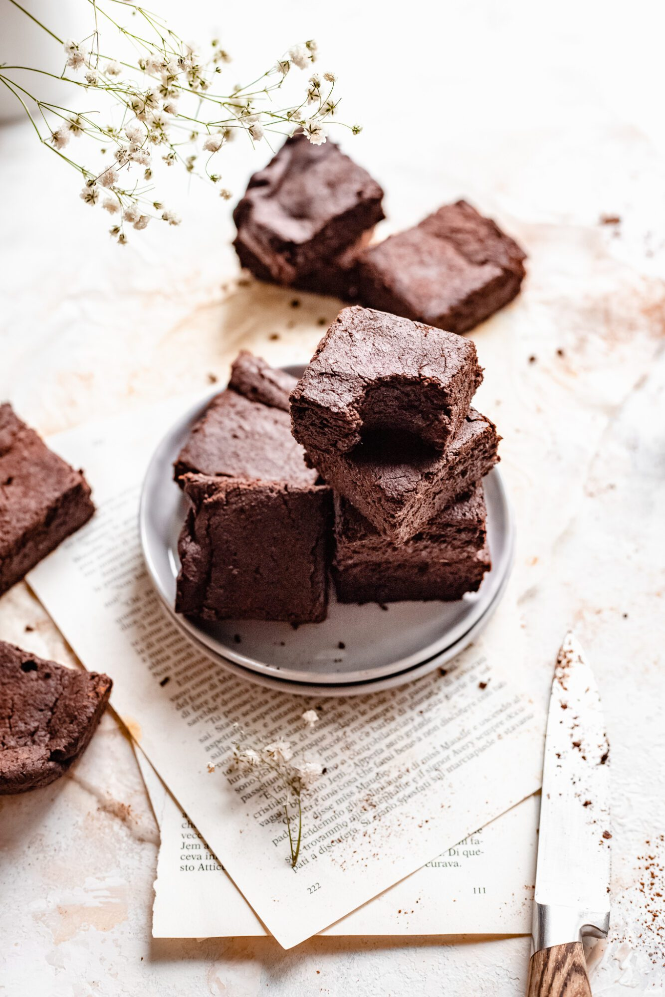 stacked vegan brownies on pages of a book