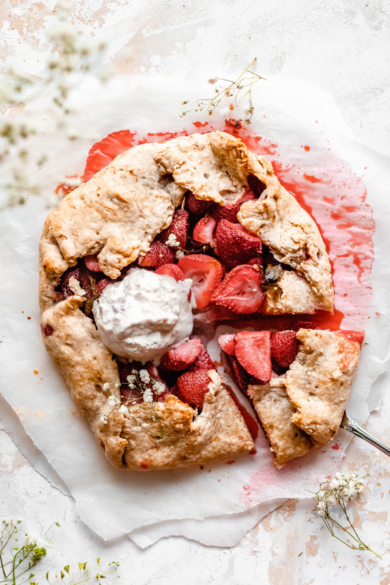 sliced strawberry galette with scoop of vanilla ice cream