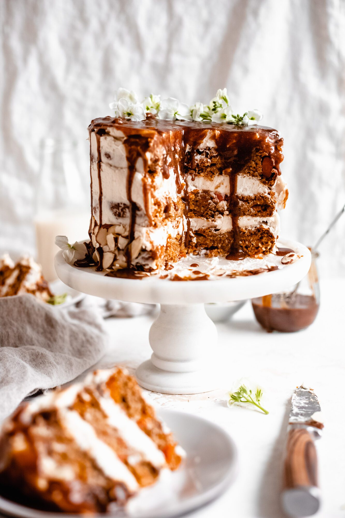 gooey carrot cake with caramel drizzle on cake stand