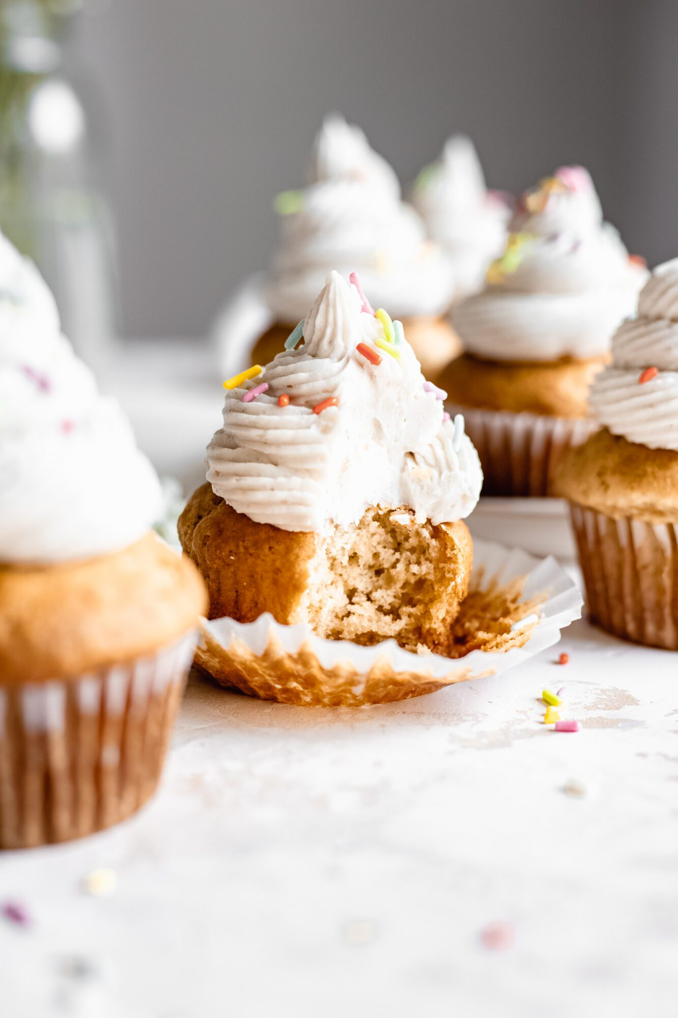 vanilla cupcake with bite taken out of it