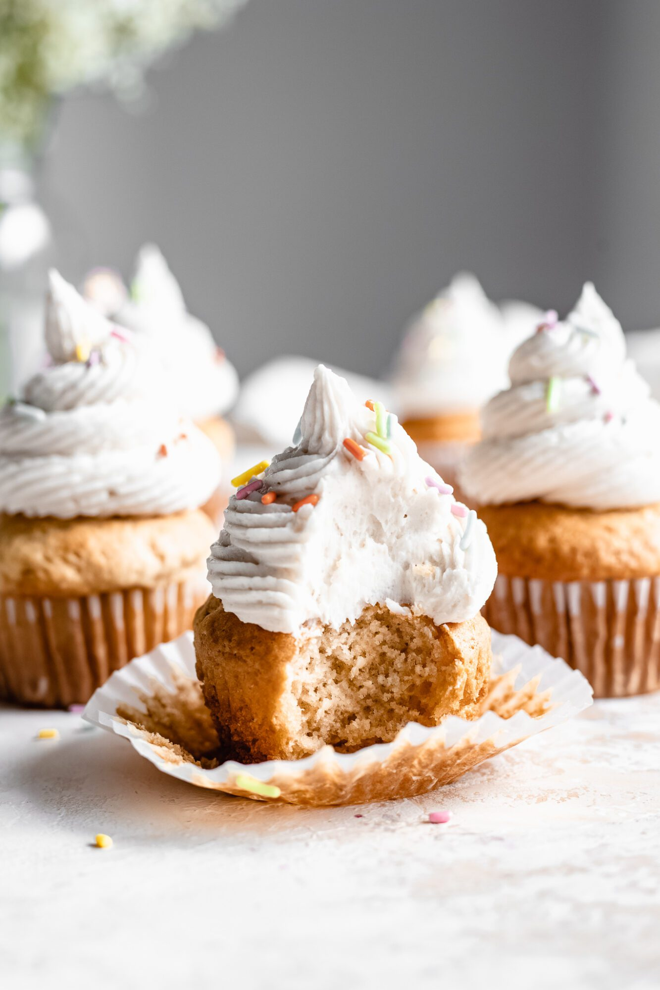 bitten veagn cupcake with vegan frosting and sprinkles